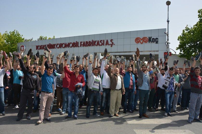 Tofaş işçileri tepkilerini ayakkabıları kaldırarak gösteriyor.